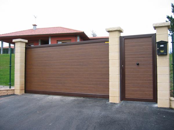 Puerta corredera imitando madera y puerta peatonal a juego.